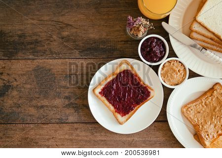 Toast bread with homemade strawberry jam and peanut butter served with orange juice. Homemade toast bread with jam and peanut butter on table for breakfast. Delicious toast bread in top view flat lay.Toast bread with spread ready to served.