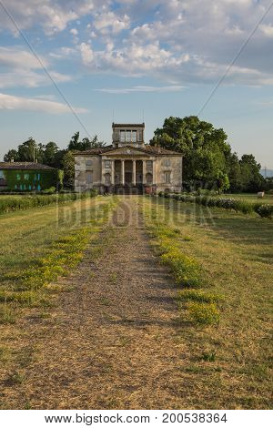 Ancient Italian Neoclassical House Inside Park And Blue Sky With Clouds
