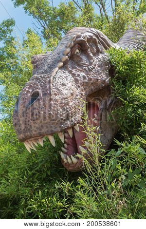 T-Rex Dinosaur Head Model among vegetation inside a Park in Italy