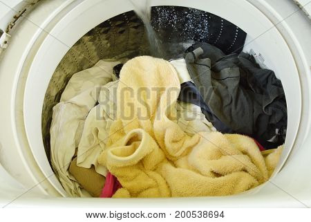 water flowing on cloth in washing machine drum operated to wash