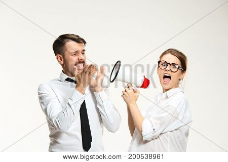 Successful business couple at the office on white background. Listening, Megaphone, Shouting concept.