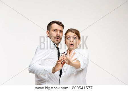 The frightened business couple at the office looking at camera on white background
