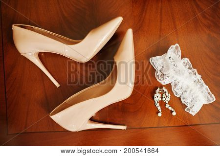 Close-up Photo Of Bridal High Heels, Earrings And Garter Laying On The Table.