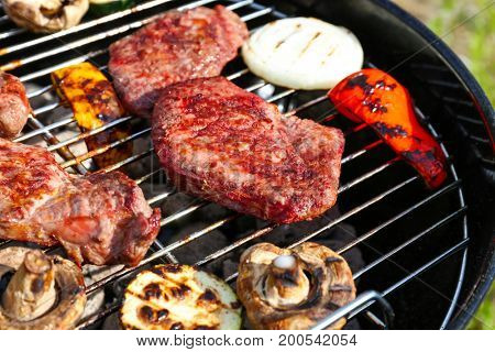 Tasty beefsteaks and vegetables cooking on barbecue grill