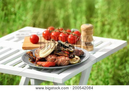 Grilled tasty beefsteaks and vegetables on white table outdoors