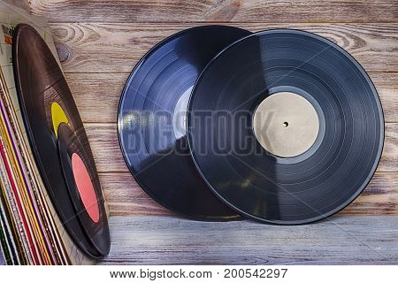 A pile of old vinyl records stand on a shelf against the background of a wooden wall