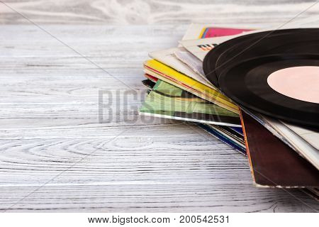 Old vinyl record on wooden background. Retro style