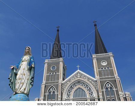 Virgin Mary statue in front of church on blue sky background