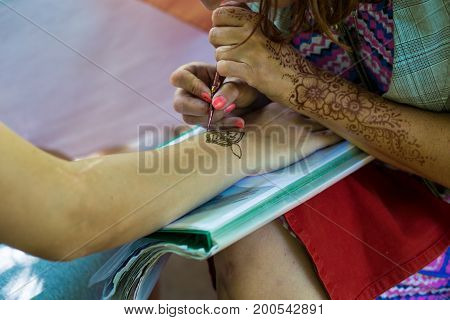 Drawing a pattern on the hands of henna. Drawing henna on the body