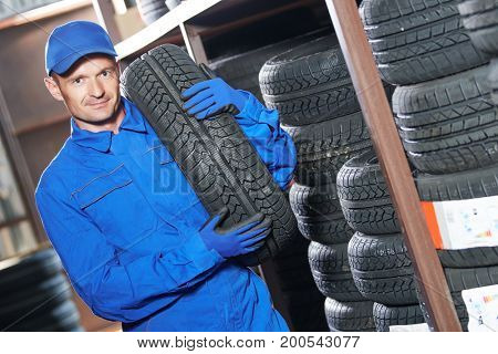 mechanic holding tire in store warehouse