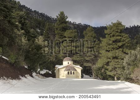Small church in the mountains in the snow, cloudy day
