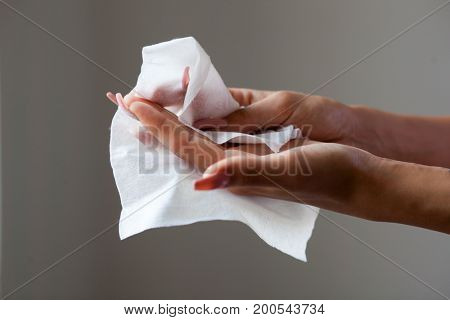 Young woman clean fingers and nails with wet wipes