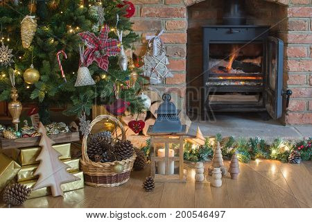 Beautiful Christmas setting, decorated lit up Christmas tree with baubles and ornaments, fireplace with woodburner , lantern, stars and garlands, selective focus