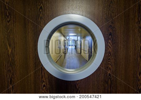 Entrance to the hospital corridor with the round window. The wooden door in the clinic.