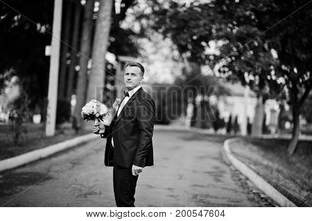 Portrait Of A Stunning Young Groom Posing On His Wedding Day On His Own. Black And White Photo.