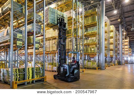 Moscow - August 1, 2017: The worker loads goods in a large warehouse. Moscow is a modern city with well-developed logistics infrastructure.
