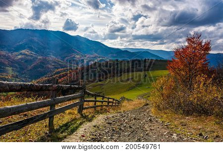 beautiful deep autumn countryside scene. wooden fence near the path through rural fields on hills in Carpathian mountainous area. Gorgeous landscape with dramatic sky over the ridge