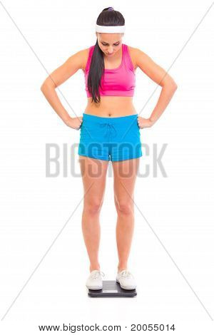 Dissatisfied with her weight young girl standing on floor scale isolated on white