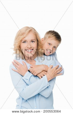portrait of smiling preteen boy hugging grandmother isolated on white