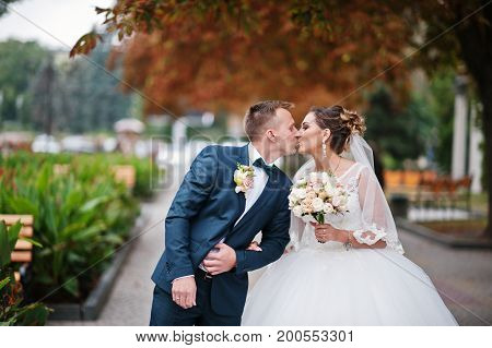 Beautiful Wedding Couple Kissing Outdoor On The Wedding Day.