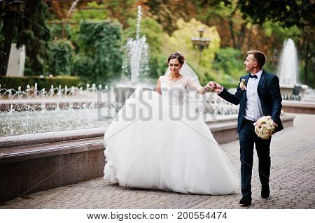 Wedding Couple Walking And Smiling On Pavement With A Fountain In The Background.
