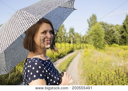 girl in polka dot dress under the scorching sun and holding a parasol.
