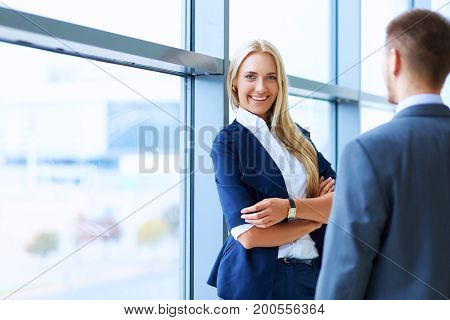 Portrait of young businesswoman in office with colleagues in the background