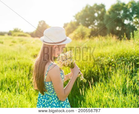 Portrait of smiling girl with bouquet of wildflowers in a field with green grass and blue sky. Beautiful teenage girl with brown long healthy hair in short dress on the field. Summer portrait.
