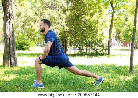 Sporty young man doing sport exercises for legs in park