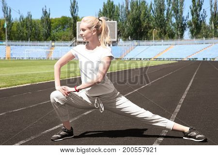 Young beautiful woman doing sport exercises for legs at stadium