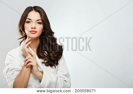Lovely Girl With Dark Hair Wearing Bath Robe At White Studio Background