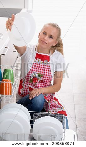 Woman Holding Plate Above Dishwasher
