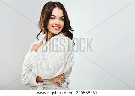 Cute Girl With Dark Hair Wearing Bath Robe At White Studio Background