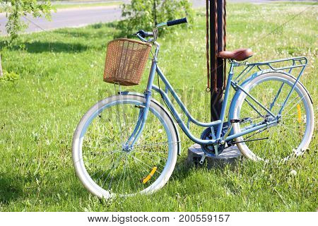 Bicycle with wicker basket on green grass in park