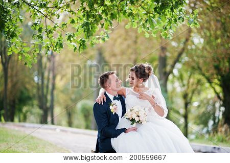 Outstanding Bride Sitting On Her Husband's Lap During Their Wedding Walk In The Park.