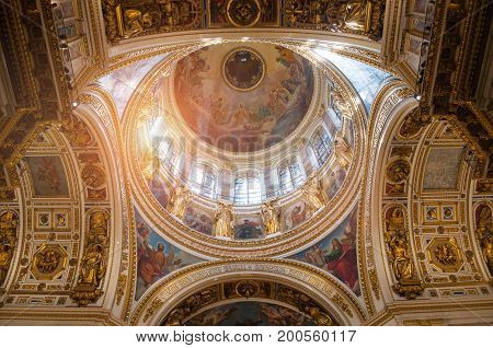 ST PETERSBURG RUSSIA - AUGUST 15 2017. Decorative elements of the ceiling - icons and decorated dome with windows - in the interior of the St Isaac Cathedral in St Petersburg Russia. St Petersburg Russia orthodox landmark inside view