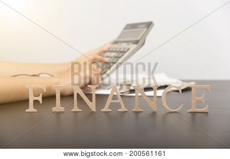 accountant with calculator and finance alphabet on desktop. concept business loan.