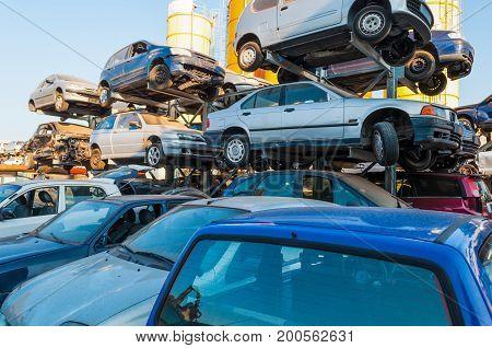 Old cars stacked in a car breaker junkyard