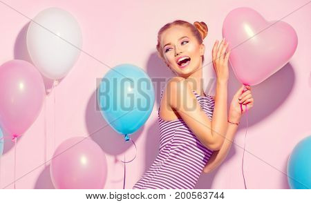 Beauty girl with colorful air balloons laughing over pink background. Beautiful Happy Young woman on birthday holiday party. Joyful model having fun, playing and celebrating with pastel color balloons