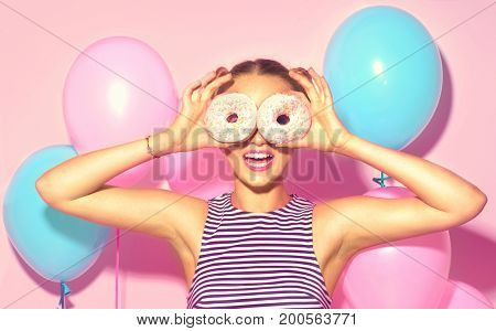 Beauty girl holding donuts and colorful air balloons laughing over pink background. Beautiful Happy Young woman on birthday holiday party with doughnuts. Joyful model Celebrating.