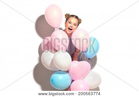 Beauty girl with colorful air balloons laughing, isolated on white background. Beautiful Happy Young woman on birthday holiday party. Joyful model having fun and celebrating with pastel color balloons