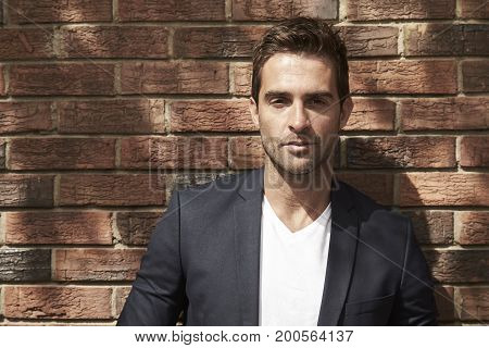Serious dude in suit jacket by wall portrait