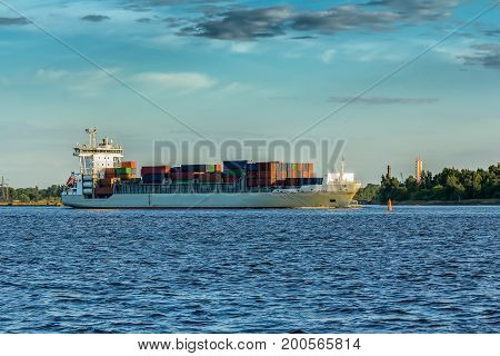 freight ship on sunset light going from port in RigaLatvia industrial transportation background