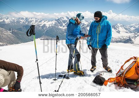A professional guide shows how to dress and set up an alpinist crampons to a beginner mountaineer before climbing
