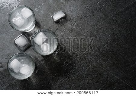 Vodka gin in shot glasses on dark stone background top view with copyspace