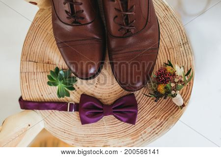 Close up of modern man accessories. purple bow-tie, leather shoes, belt and flower boutonniere on wood chair rustic background.