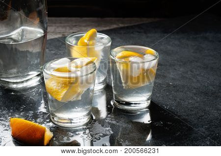 Bottle of vodka or gin with shot glasses and lemon. On stone background.