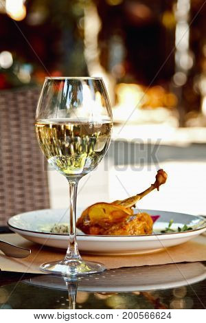 Duck Leg Config With Sauce And Glass Of White Wine In Restaurants