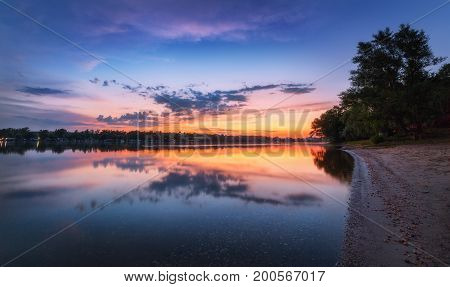 Tranquil Scene With River And Colorful Sky With Clouds At Sunset