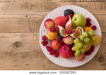 Top view on assortment of juicy fruits on white plate and wooden table background..Organic raspberries apricots apples figsplums grapes - summer dessert or snack.healthy eating concept.